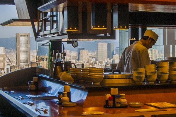 A chef prepares for the evening rush in Umeda, with Osaka Business Park visible in the background - Osaka