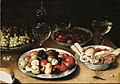 Osias Beert - Still life of plums, nuts and apples, raspberries and sweetmeats in three blue-and-white porcelain bowls, with grapes on a pewter dish, a façon-de-venise goblet, wine-glasses and bread.jpeg