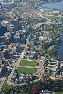 An aerial view of Parliament Hill from the southeast looking northwest along Wellington Street.  The three green copper-roofed buildings at lower centre are the East, Centre, and West Blocks of Parliament.