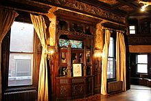 This is a photo of the Payne Mansion( Pi Kappa Phi Fraternity House) Dining room showing a Tiffany stained glass window, built in buffet, cherry inlaid floors and the choir loft.
