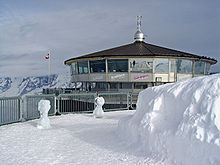 A restaurant in a snowy environment. Mountains can be seen in the background.