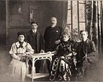 Old photo of five Pontic Greeks in western dress, seated or standing inside.