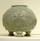 A blue-green tinted grey pot with a wide bottom supported by three stubby legs, a wide body, and a smaller opening at the top. A large five petal flower pattern is out-dented on the body of the jar.