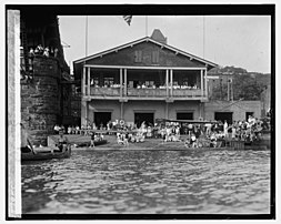 Potomac Boat Club from the Potomac River with various rowers standing outside Club building
