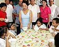 """President Gloria Macapagal-Arroyo enjoins one of the malnourished children to eat """"sopas"""" during a feeding program acitivity 03.jpg"""