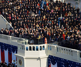 View of a large portion of a large ceremony with visible red, white and blue ornamentation and a crowd of attendees