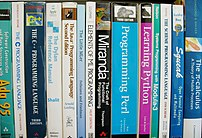 A selection of programming language textbooks on a shelf. Levels and colors adjusted in the GIMP.