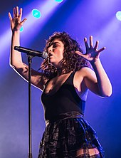 Lorde performing onstage against a purple background