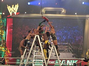 Seven professional wrestlers battle on top of four ladders in the ring, reaching for a red briefcase hanging above them.