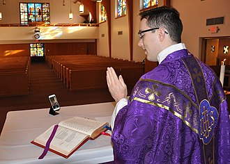 An American Catholic military chaplain prepares for a live-streamed Mass in an empty chapel at Offutt Air Force Base in March 2020. Religious service live-streaming during the 2020 coronavirus pandemic.jpg