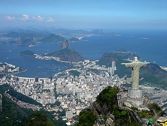 Christ the Redeemer (statue) - A panoramic view of the statue at the top of Corcovado Mountain with Sugarloaf Mountain (centre) and Guanabara Bay in the background.