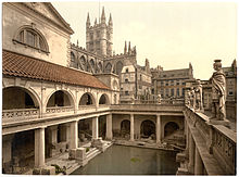 A late-nineteenth century Photochrom of the Great Bath at the Roman Baths. Pillars tower over the water, and the spires of Bath Abbey – restored in the early sixteenth century – are visible in the background.