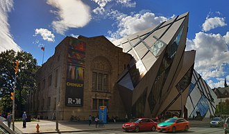 "The Royal Ontario Museum was originally designed in a Romanesque Revival style, although other styles have since been added to the building. Architecture in Toronto has been called a ""mix of periods and styles"". Royal Ontario Museum, Toronto (29881909163).jpg"