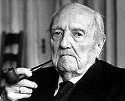 En format paysage, photographie d'un visage d'homme âgé, chauve et triste à droite portant une pipe entre les doigts de sa main à gauche. En fond: intérieur de maison.