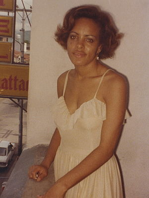 1980s in Western fashion - Young woman in 1980 wearing a low-cut spaghetti strap dress.