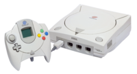 An NTSC Sega Dreamcast Console and PAL Controller with VMU.