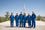 Soyuz TMA-09M crew and backup crew in front of a Proton rocket statue.jpg