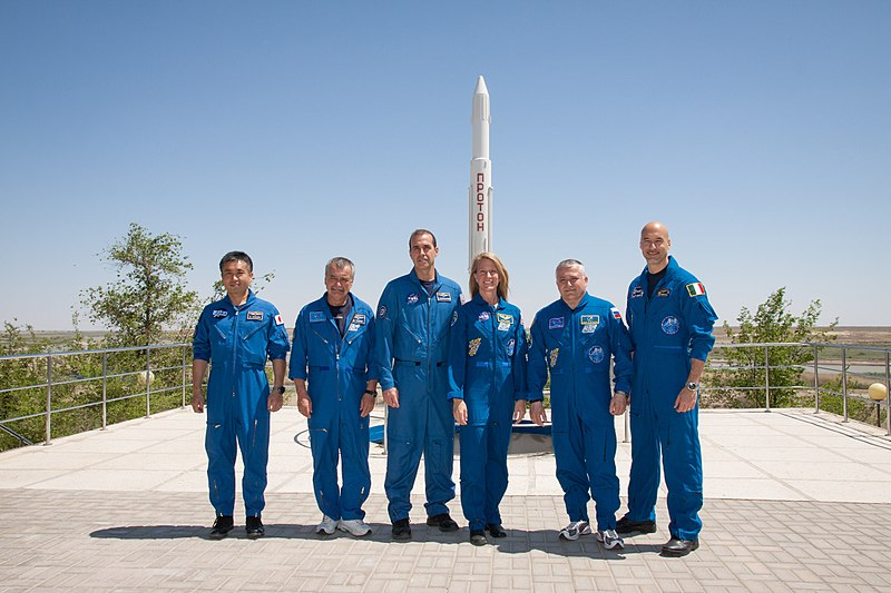 File:Soyuz TMA-09M crew and backup crew in front of a Proton rocket statue.jpg