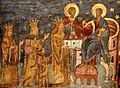 A bearded man who wears a crown offers a church to Christ who sits on a throne; the man is surrounded by a crowned woman and man and a child