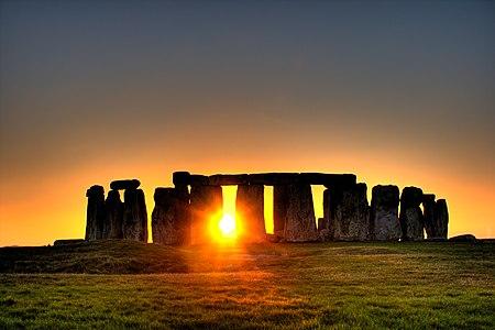 الشمس تشرق من خلف صف من الحجارة المنتصبة تقبع عليها صخور أخرى أفقية.