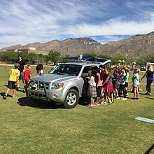 Students looking at self-driving car on school field.