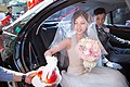 Taiwanese brides touching the apples while sitting in the wedding car.jpg