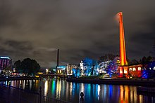 A 2015, night picture of the Tammerkoski rapids in Tampere. The Festival of Light has just opened and an old, large factory chimney is lit in warm red on the right side of the rapids and contrasts with the cool blue lighting of the trees beneath it. The array of colours is reflected wondrously by the water of the rapids. The city was a central point both ideologically and strategically during the Finnish Civil War and its build-up, such as the general strike of 1905.