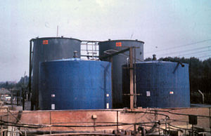 A bund wall surrounds industrial large tanks