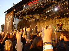 Turunen with her support band in front of a crowd at the Wacken Open Air.