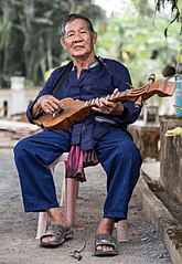 A Thai Lue musician plays in the garden of Wat Nong Bua, Tha Wang Pha District, Thailand