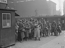 Scene at London Victoria station of troops on leave being directed by a member of the Volunteer Training Corps