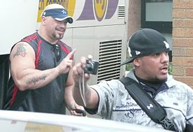Two adult Latino males, one doing hand signs and another holding a camera.
