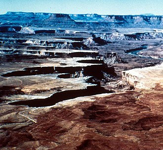 Groundwater sapping - The two canyons at center-left in this photo from Canyonlands National Park in Utah have the theater-shaped heads typical of valley features shaped by groundwater sapping. The Green River is at right.