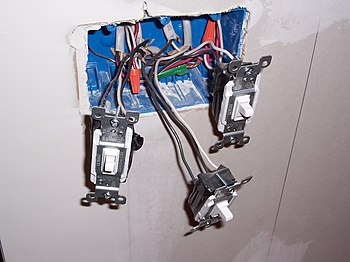 Three light switches with exposed wiring