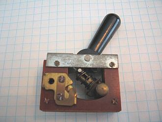 "Switch - Large toggle switch, depicted in circuit ""open"" position, electrical contacts to left; background is 1/4"" square graph paper"