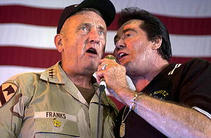Wayne Newton - Gen. Tommy Franks, Commander, U.S. Forces Central Command (CENTCOM) sings a duet with Wayne Newton aboard the USS Nimitz during a USO show. At the time, the USS Nimitz was deployed to the Persian Gulf in support of Operation Iraqi Freedom. June, 2003.