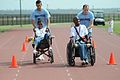 U.S. Air Force Airman Basic Tyler Hewitt, left, pushes Veronica Nickelson and Airman 1st Class Adam Trochesset pushes Roderick Smith while competing in the 25-meter assisted wheelchair race at the 2010 100515-F-BD983-009.jpg