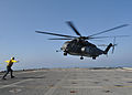 U.S. Navy Aviation Boatswain's Mate Fuel Airman Adam M. Pond signals an approaching MH-53E Sea Dragon helicopter assigned to Helicopter Mine Countermeasures Squadron (HM) 14 to land on the flight deck of 100917-N-PV215-029.jpg
