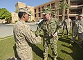 U.S. Navy Vice Adm. John W. Miller, center, commander of U.S. Naval Forces Central Command, U.S. 5th Fleet, Combined Maritime Forces, shakes hands with Hospital Corpsman 2nd Class James Matos, assigned to Fleet 130828-N-VY489-090.jpg