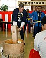 US Navy 031219-N-8726C-002 Capt. Wayne Radloff, Commanding Officer, Naval Air Facility Misawa, pounds rice into a cake.jpg
