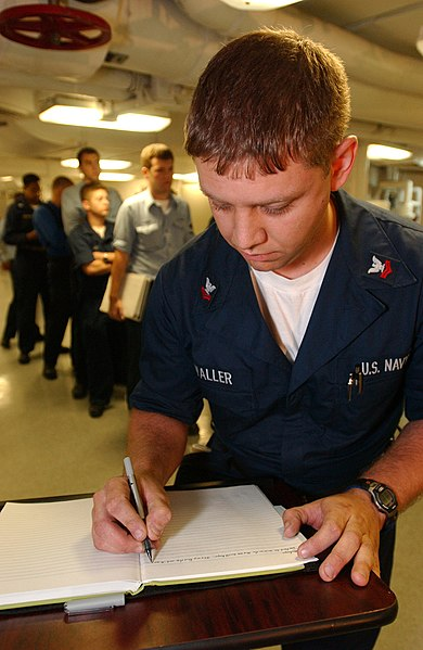 File:US Navy 040607-N-2788L-191 Machinist Mate 2nd Class Thomas Waller, from Lexington, Neb., writes a personal message in a book, which is going to be presented by USS Ronald Reagan's (CVN 76) Commanding Officer, Capt. James A. Sym.jpg