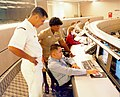 US Navy 040614-N-7952W-001 Information Systems Technician 1st Class Thomas Dull, left, Lt. Stella Nealy, center, and Information Systems Technician 2nd Class Eduardo Pallanes study a computer monitor at Naval Network and Space.jpg