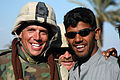 US Navy 050103-N-5386H-155 Steelworker 2nd Class Chad Larsen, assigned to Naval Mobile Construction Battalion Seventeen (NMCB-17), poses for a photo with a Haidiriyah resident.jpg
