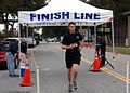 US Navy 061027-N-5455M-007 Mass Communication Specialist 3rd Class Andy King crosses the finish line before the rest of his shipmates assigned to USS Nassau (LHA 4) during the Naval Station Norfolk 2006 Monster Dash 5K race.jpg