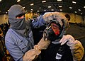 US Navy 070320-N-7981E-202 Personnel Specialist 1st Class John Smith helps Personnel Specialist 1st Class Bernardino Bardos don a Self Contained Breathing Apparatus (SCBA) used for fire fighting during a general quarters drill.jpg