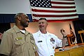US Navy 090610-N-9818V-104 Master Chief Petty Officer of the Navy (MCPON) Rick West presents Gunner's Mate 1st Class James Glenn with a MCPON challenge coin.jpg