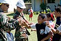 US Navy 090717-N-9689V-011 Lt.j.g. Christian Auger of Naval Mobile Construction Battalion (NMCB) 1 and Lt.j.g. Shawn Talley of Amphibious Construction Battalion (ACB) 1 say good-bye to schoolchildren after playing a game of ba.jpg