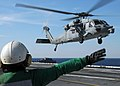 US Navy 100308-N-7908T-149 A Sailor assigned to Helicopter Sea Combat Squadron (HSC) 9 signals to an MH-60S Sea Hawk helicopter as it takes off from the aircraft carrier USS George H.W. Bush (CVN 77).jpg