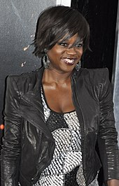 Viola Davis, wearing a leather jacket, against a black background