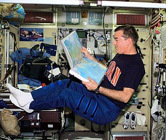 Expedition 2 - James S. Voss, Expedition Two flight engineer, looks over an atlas in the Zvezda Service Module. (NASA)